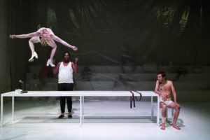 Cast member suspended from the stage roof: Siphenathi Mayekiso, Mncedisi Shabangu and Charlton George in 'Marat/Sade'. Photograph: Oscar O' Ryan