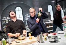 Host Alton Brown watches Chef Shota Nakajima prepares his dish, Honey Mustard Szechuan Shrimp, for the Chairman's Challenge, as seen on Iron Chef Gauntlet, Season 1